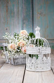 Vintage birdcage, beautiful pink roses and gypsophila paniculata — Stock Photo