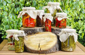 Jars of preserves on wooden table in the garden — Stock Photo