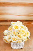 Bouquet of ecru roses in wicker basket. Wooden background, copy — Stockfoto