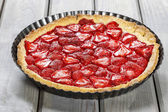 Strawberry tart isolated on wooden table — Stock Photo