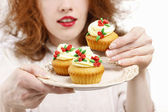 Eat or not to eat: woman hesitating over the plate with rose cup — Stock Photo
