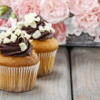Fancy chocolate cupcakes on wooden table. Pink carnation flowers — Stock Photo #47974495