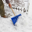 Man removing snow from the sidewalk after snowstorm — Stock Photo #47975097