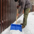 Man removing snow from the sidewalk after snowstorm — Stock Photo #47975103