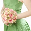 Young woman in green dress holding bouquet of pink roses — Stock Photo #47975659