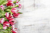 Beautiful red tulips and carnations on wooden table. Top view, c — Stock Photo