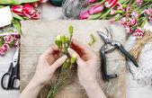 Florerias en el trabajo. mujer haciendo adornos florales de la primavera — Foto de Stock