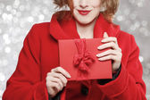 Glamorous woman holding red present box with big bow — Stock Photo