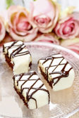Chocolate and marzipan wedding cakes on glass cake stand. Bouque — Stock Photo