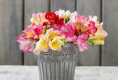 Bouquet of colorful freesia flowers in silver bucket — Stock Photo