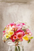 Bouquet of colorful freesia flowers in transparent glass vase. — Stock Photo