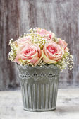 Bouquet of pink roses in rustic bucket — Stock Photo