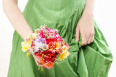 Young woman in green dress holding bouquet of colorful freesia f — Stock Photo
