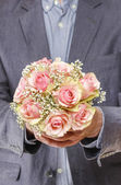 Man holding bouquet of pink roses — Stock Photo