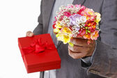 Man holding colorful bouquet of freesia flowers and red box with — Stock Photo