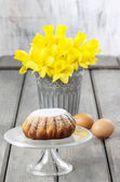 Daffodils in silver bucket on grey wooden table and easter yeast — Stock Photo