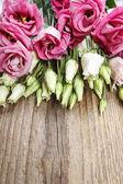 Kytice růžových eustoma na dřevěný stůl — Stock fotografie