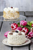 Round vanilla cake on cake stand. Beautiful bouquet of pink and  — Stock Photo