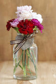 Colorful carnation flowers in transparent glass vase on wooden b — Stock Photo