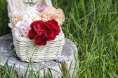 Beautiful carnation flowers in a white wicker basket — Stock Photo