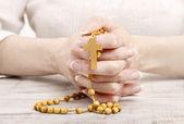 Vrouw met houten rozenkrans in mooie handen — Stockfoto