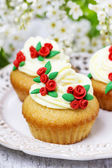 Beautiful rose cupcake and bird cherries in the background — Stock Photo