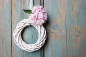 White wicker wreath on wooden door — Stockfoto