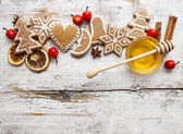 Gingerbread christmas cookies and bowl of honey on wooden table. — Stock Photo