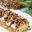 Fruitcake with dried fruits and nuts in christmas setting — Stock Photo #48063631