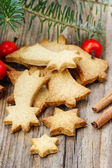 Christmas cookies on wooden table under fir branch. — Stock Photo