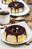 Delicious donut with chocolate on wooden table — Stock Photo