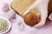 Woman decorating muffins — Stock Photo