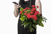Woman ordering flowers via mobile phone — Stockfoto