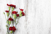 Bouquet of red carnation flowers on wooden background. Top view, — Stock Photo