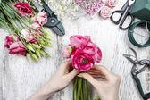 Florist at work. Woman making beautiful bouquet of pink persian — Stock Photo