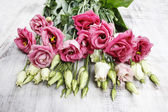 Bouquet of pink eustoma flowers on wooden table — Stockfoto