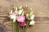 Bouquet of pink eustoma flowers on wooden table — Stock fotografie