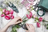 Florist at work. Woman making beautiful bouquet of pink eustoma — Stock Photo