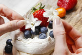 Woman decorating meringue cake with edible flowers and fresh fru — Stock Photo