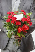 Man holding bouquet of red carnations — Stockfoto