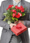 Man holding bouquet of red carnations and red gift box with big  — Стоковое фото