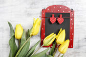 Beautiful yellow tulips and cute red and black chalkboard on woo — Stockfoto