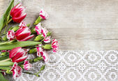 Beautiful pink tulips and carnations on wooden background — Stockfoto