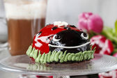 Ladybug cake and cup of hot chocolate in the background — Stock Photo