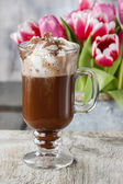 Irish coffee on wooden table. Bouquet of pink and red tulips in  — Stockfoto
