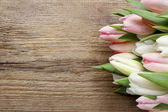 Beautiful pink and white tulips on wooden background. Copy space — Stockfoto