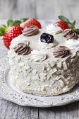 Round vanilla cake on cake stand. Fresh strawberries in the back — Stock Photo