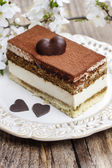 Tiramisu cake on white plate. Blossom apple branch in the backgr — Stockfoto