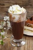 Irish coffee on wooden table. Tiramisu cake and blooming apple b — Stock Photo