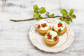 Beautiful rose cupcake and blooming apple tree twig in the backg — Stock Photo